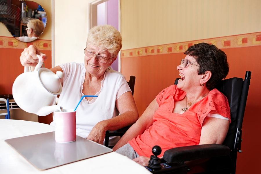 carer making tea for happy disabled woman